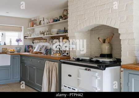 Whitewashed kitchen with crockery on open shelving and grey fitted units in 18th century Norfolk cottage - Stock Photo