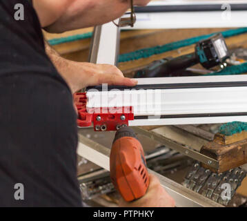 Production of pvc windows, a man screws a screwdriver into a pvc window, close-up, windows pvc - Stock Photo