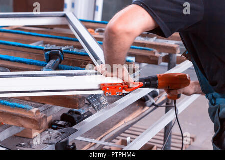 Production windows pvc, man screwed screwdriver hinged defense on the sash pvc frame, close-up, work, process - Stock Photo