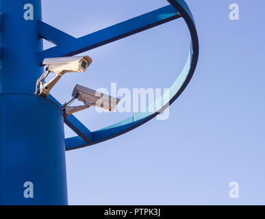 Two CCTV cameras on a blue pillar against a blue sky background - Stock Photo