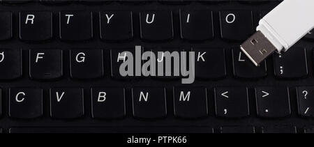 White USB flash drive on a black keyboard, close-up - Stock Photo