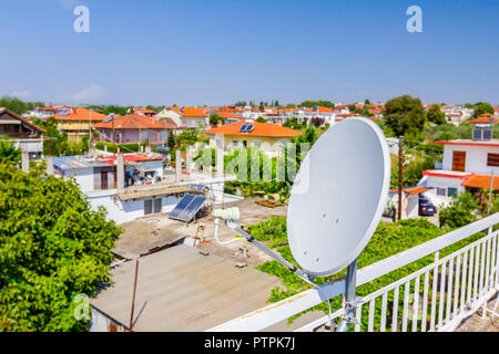 Satellite antenna dish is placed on house rooftop, external unit. - Stock Photo