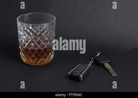Car keys and glass with alcohol whiskey on black background, close-up - Stock Photo