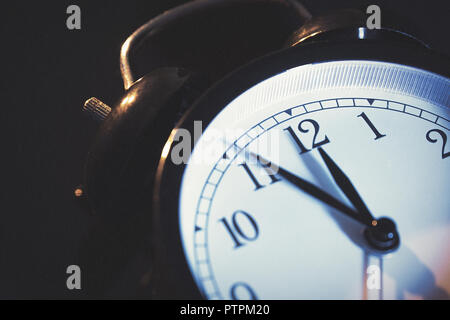 Five minutes to midnight. Changing the clocks, time adjustment, daylight savings or new year concept on retro analog clock.