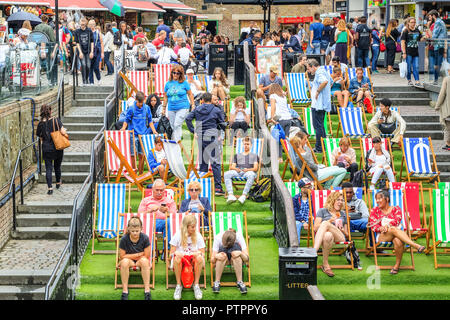 London, UK - September 1, 2018 - Tourist relaxing on deckchairs at crowded Camden Market - Stock Photo