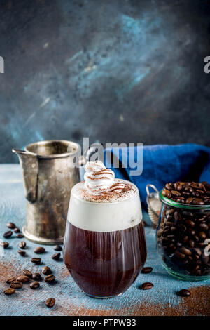 Autumn espresso drink ideas, Irish coffee cocktail with whipped cream and cocoa, blue concrete background copy space