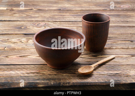 Set of clay dishes with tablecloth on wooden table - Stock Photo