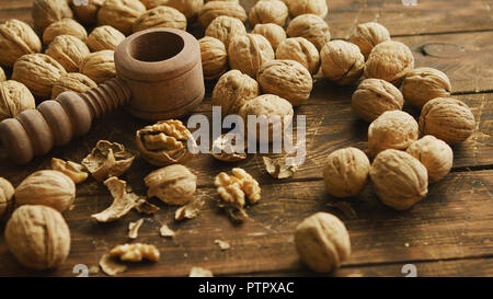Walnuts and nutcracker on table - Stock Photo