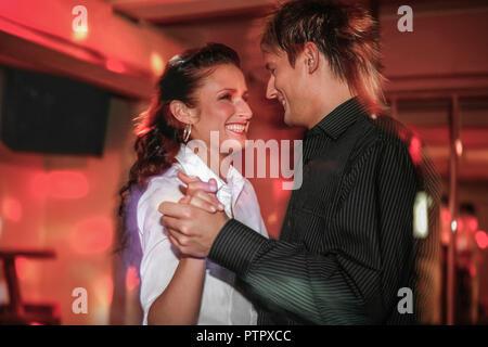 junges verliebtes Paar beim Tanzen in einer Disco (Modellfreigabe) - Stock Photo