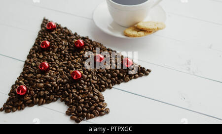 Coffee beans in shape of conifer and cup - Stock Photo