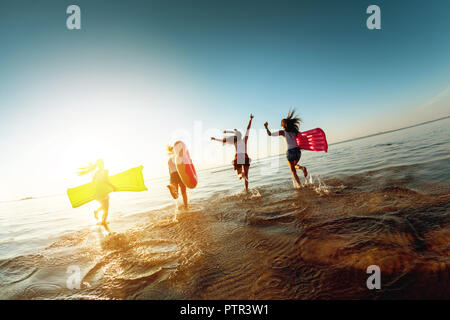 Four happy girls having fun and runs to sunset lake - Stock Photo