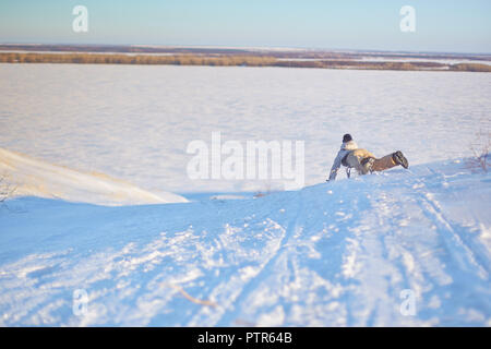 Cheerful girl riding a sled downhill on a snow covered sledge trail in a white sunny winter mountain landscape. - Stock Photo