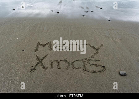 Wet sand and Merry Xmas hand written in the sand. - Stock Photo