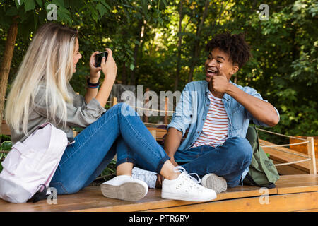 Happy young multiethnic couple spending time together at the park, taking photo of each other - Stock Photo