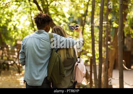 Back view young multiethnic couple spending time together at the park, walking, hugging - Stock Photo