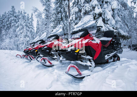 Group of four brightly colored red and black snowmobiles are ready for adventure ride. Vehicles parked in line near beautiful forest in Lapland, Finla - Stock Photo
