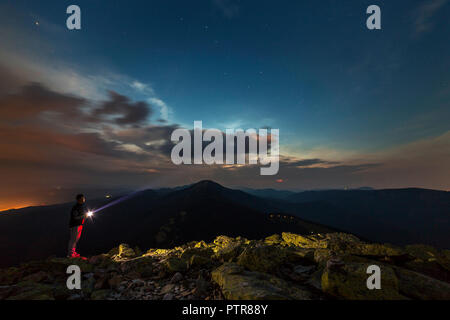 Beautiful summer night in mountains. Profile silhouette of young tourist hiker man with flashlight standing alone on rocky mountain peak under starry  - Stock Photo