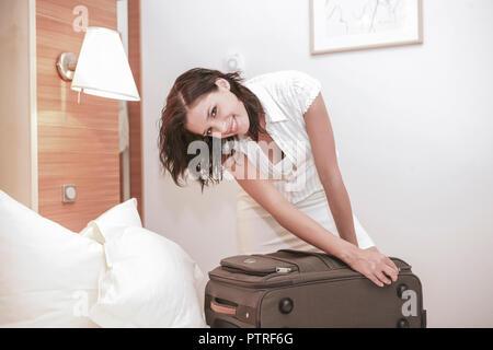 Reisevorbereitung, Frau, Bett, Koffer, packen, Reissverschluss, schliessen, Reisevorbereitungen, Kofferpacken, einpacken, Reisegepaeck, Gepaeck, Vorfr - Stock Photo
