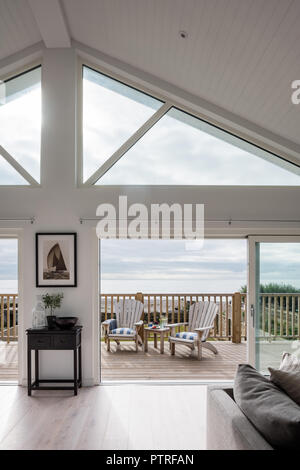 Black and white maritime photo of the Isle of Wight over table with view through doorway to decked terrace and West Wittering beach - Stock Photo