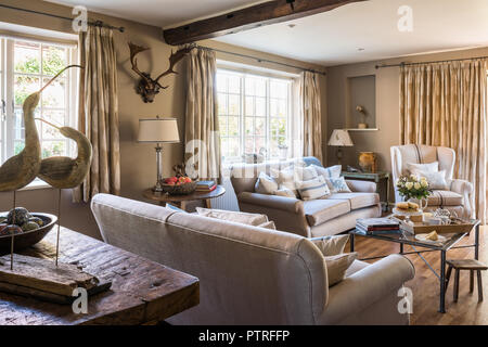 Neutral sofas with wall mounted antlers and bird ornaments in restored 16th century farmhouse - Stock Photo