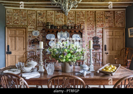 Decorative chinaware on antique wooden dresser with table and chairs in restored 16th century farmhouse - Stock Photo