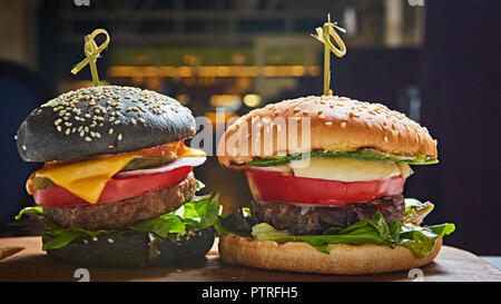 Set of homemade burgers in black and white buns with tomato, lettuce, cheese, onion on wood serving board over dark table. Rustic style. Homemade fast food. - Stock Photo