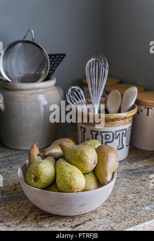 Bowl of pears with utensils in ceramic pots in 16th century farmhouse renovation - Stock Photo