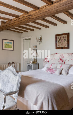 Embroidered folk art above double bed in beamed 16th century farmhouse renovation - Stock Photo