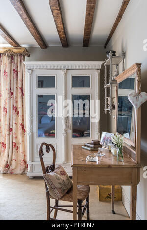 Glass fronted cabinet with floral curtains and wooden dressing table with wicker chair in 16th century farmhouse renovation - Stock Photo