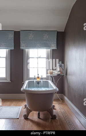 Running taps on freestanding bath with light blue emboidered curtains at window in restored 16th century farmhouse - Stock Photo
