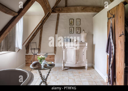 Mannequin on sideboard with botanical prints in restored 16th century farmhouse bathroom - Stock Photo