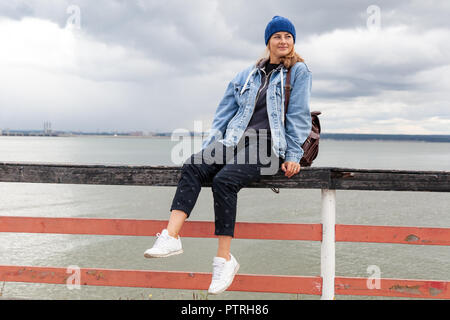 Portrait of a beautiful young model in blue knitted hat sit near sea. Autumn warm photo.Woman smiling and look away, joyful cheerful mood. - Stock Photo