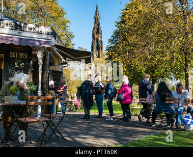 Princes Street Gardens, Edinburgh, Scotland, UK, 10th October 2018. UK Weather: People sit in the warm sunshine among the Autumn tree colours and queue to buy ice cream from a food stall - Stock Photo