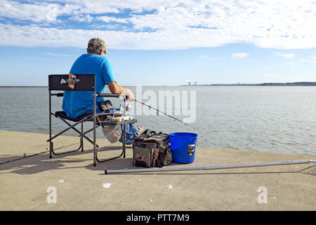Fairport Harbor, Ohio, USA, 10th Oct, 2018.  A man fishes in Fairport Harbor with a view of the Perry Nuclear Power plant in the distance.  Record-high temperatures this week in Northeast Ohio has extended summer bringing people outdoors to enjoy the last blast of summer.  Monday's weather in Cleveland hit an all-time high of 89(f) degrees, Tuesday tied the record high, and today saw the temperatures near historic highs with the high reaching 85(f).  The typical early October high temperature is in the mid-60's.  Credit: Mark Kanning/Alamy Live News. - Stock Photo