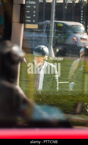 Parliament Square, London, UK. 10 October, 2018. Boris Johnson MP, former Foreign Secretary, seen through the windows of a London bus as he leaves Parliament by bike at mid-day. Credit: Malcolm Park/Alamy Live News. - Stock Photo