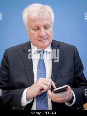 11 October 2018, Berlin: Horst Seehofer (CSU), Federal Minister of the Interior, Building and Home Affairs, looks at his mobile phone at the beginning of the presentation of the situation report of the Federal Office for Information Security (BSI). The BSI is responsible for defending against cyber attacks and advises associations and companies. Photo: Kay Nietfeld/dpa - Stock Photo