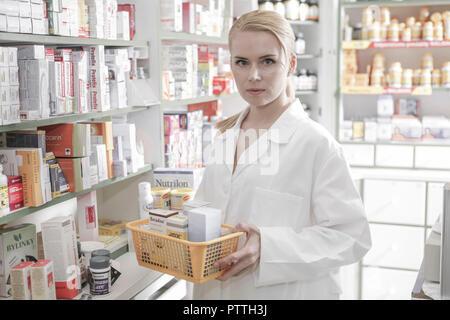 Apothekerin, Apothekerschrank, entnehmen, Apotheke, Frau, 20-30 Jahre, Angestellte, PTA, Arbeit, Job, Beruf, Pharmazeutin, Medizin, Arzneimittel, Medi - Stock Photo