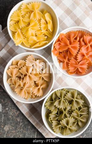 Farfalle pasta. Colorful italian pasta in bowl on old kitchen table. - Stock Photo