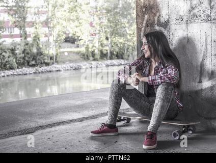 Junge Frau sitzt auf Longboard (model-released) - Stock Photo