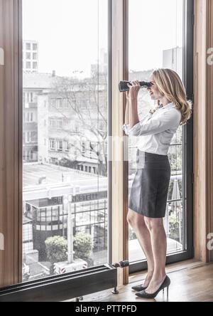 Frau schaut mit einem Fernglas aus dem Fenster (model-released) - Stock Photo