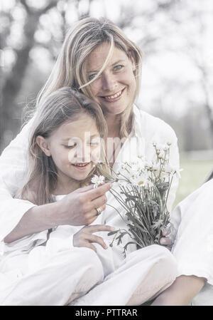 Mutter sitzt mit Tochter und Margeritenstrauss auf Wiese (model-released) - Stock Photo
