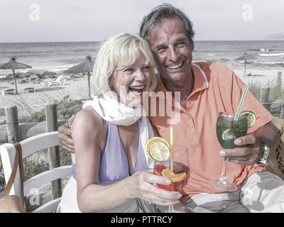 Aelteres Paar sitzt mit Cocktails an Strandbar (model-released) - Stock Photo