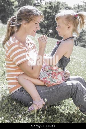 Mutter sitzt mit Tochter auf Wiese (model-released) - Stock Photo