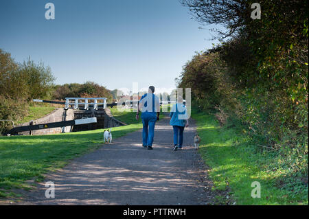 Walkers and their dogs on the towpath at the Caen Hill Flight on the Kennet and Avon Canal, Devizes, Wiltshire, UK. - Stock Photo