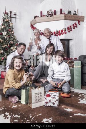 Familie sitzt mit Grosseltern vor Weihnachtsbaum (model-released) - Stock Photo