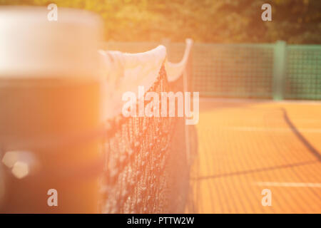 close-up tennis net on court with sunlight in background - Stock Photo