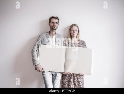 Junges Paar mit Tapetenbuch in neuer Wohnung (model-released) - Stock Photo