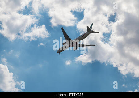 Emirates' Boeing 777 landing against blue sky and clouds - Stock Photo