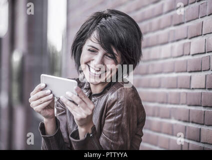 Junge dunkelhaarige Frau schaut auf ihr Smartphone (model-released) - Stock Photo