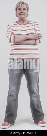 Seniorin in Jeans und Pulli, verschraenkte Arme (model-released)